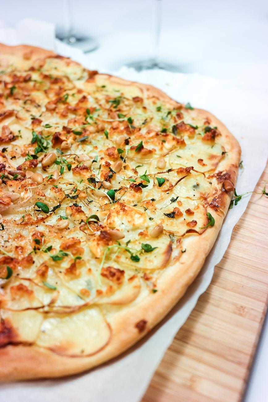 Verdens beste pizza har hvit saus, potet i løvtynne skiver, feta og masse friske urter på.