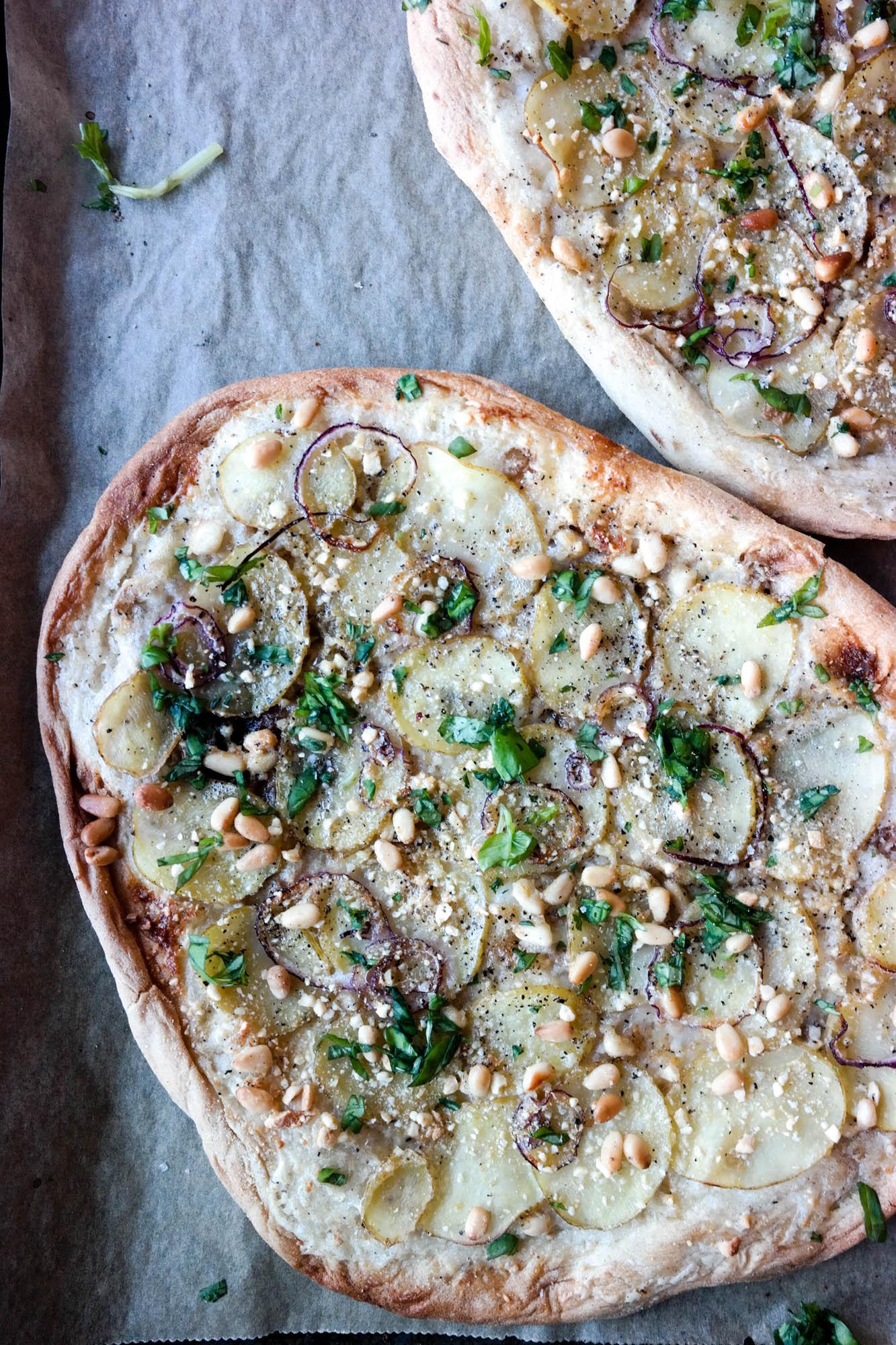 Favorittpizzaen har hvit saus, tynne potetskiver og pinjekjerner på toppen.